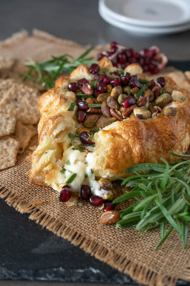 Creamy brie oozing out from the puff pastry with pomegranate seeds and pistachio nuts