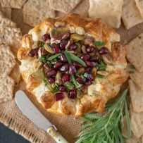 Puff pastry wrapped brie topped with nuts and pomegranate seeds served with crackers