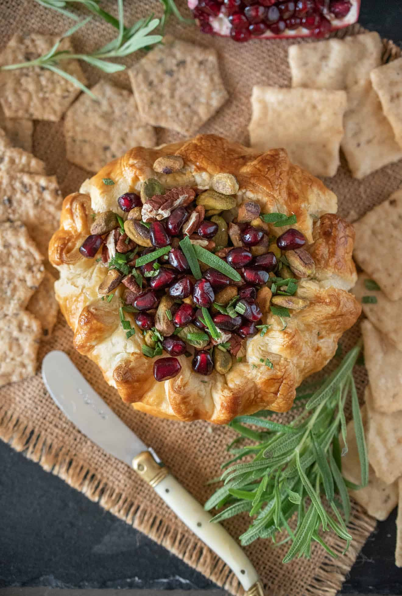 Baked Brie with Pistachios, Pomegranate and Rosemary wrapped in puff pastry surrounded with crackers
