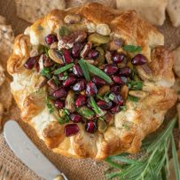 Vibrant pomegranate seeds with rosemary leaves top a baked brie that is wrapped in puff pastry served with a knife