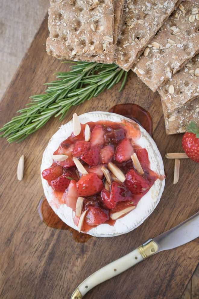 A wheel of brie topped with strawberries, fresh rosemary and almonds on a board with a knife and crackers