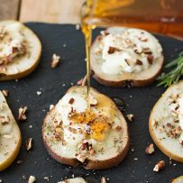 Pouring honey over baked pear slices with goat cheese and chopped pecans