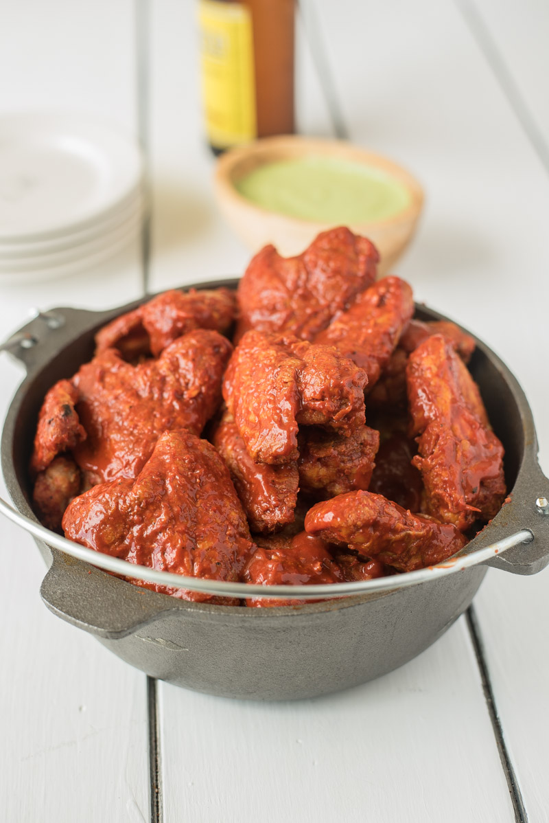 A cast iron pan full of adobo chicken wings with avocado cream for dipping
