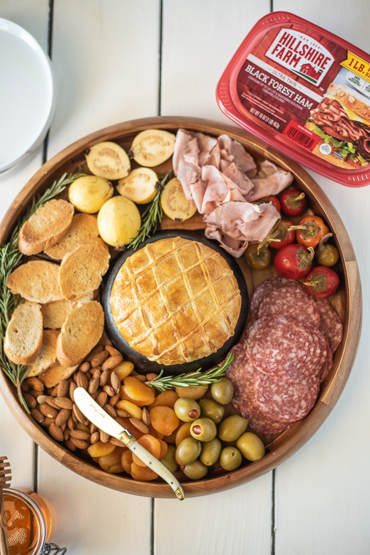 An overhead image showing baked brie on a charcuterie board with a tub of Hillshire Farm Black Forest Ham