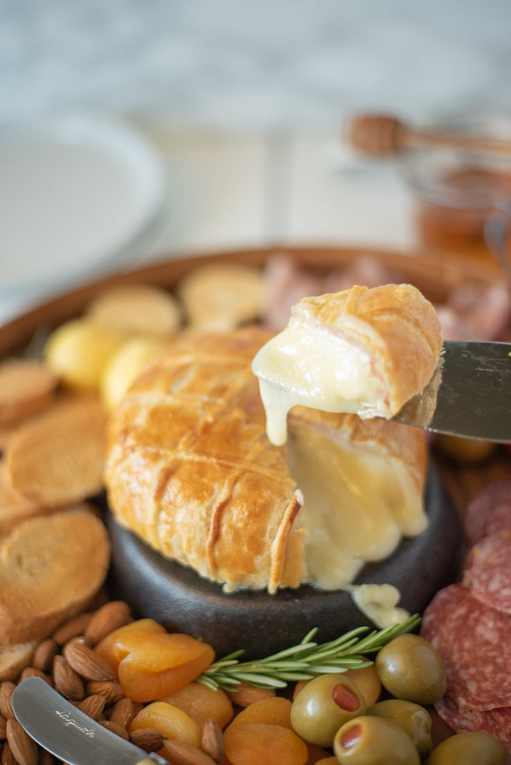 A cheesy, melted slice of Baked brie and Black Forest ham in puff pastry on a knife