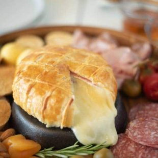 A cut open Baked Brie and Black Forest ham in puff pastry with lots of melted brie oozing out