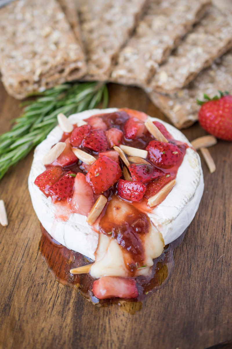 A wheel of brie on a board with melted cheese oozing out topped with strawberries