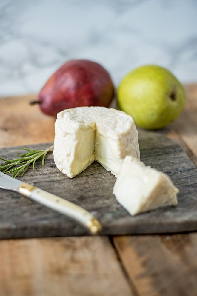 A block of good goat cheese with a knife