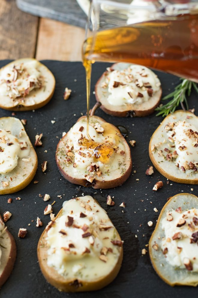 Drizzling honey over baked pears with goat cheese and pecans