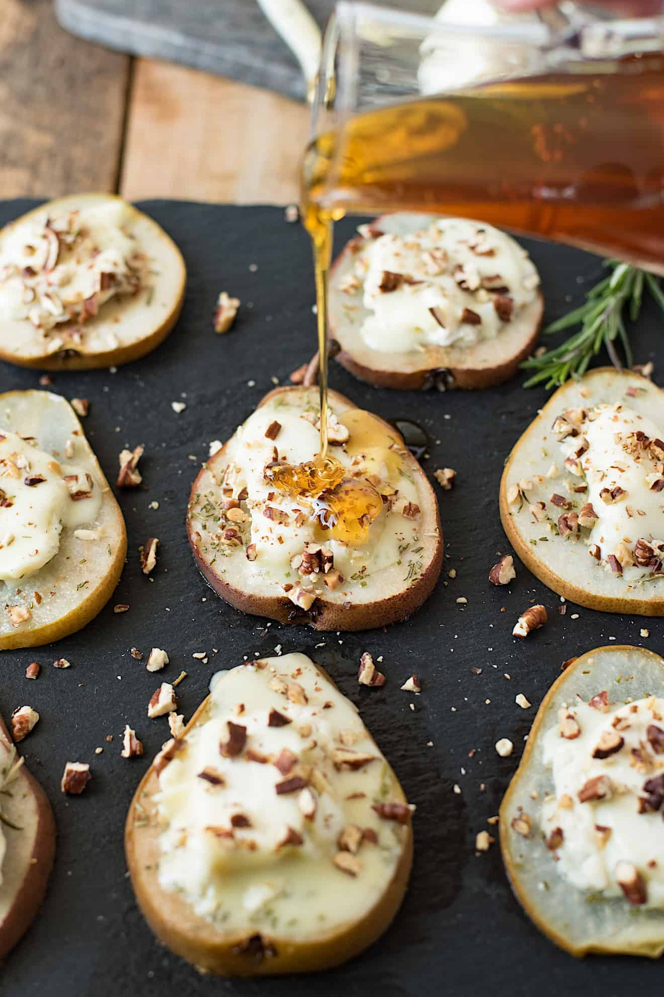 Pear slices on a platter topped with goat cheese, pecans and honey