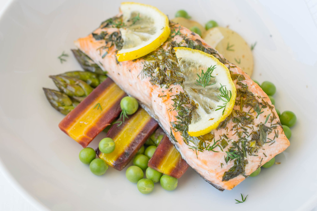 Baked salmon with spring vegetables can be on the table in about 30 minutes. They're baked in parchment paper and served this way, so cleanup is a springtime breeze.