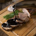 Juicy pork tenderloin slices being drizzled with thick balsamic glaze