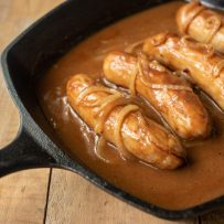 Sausage bangers in a pan with onion gravy