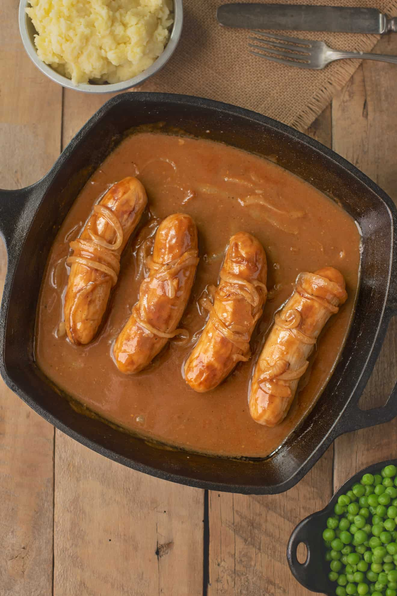 4 British bangers in a cast iron skillet cooking in onion gravy