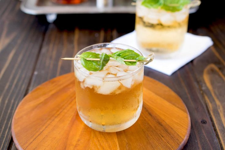 A glass of basil julep on a board