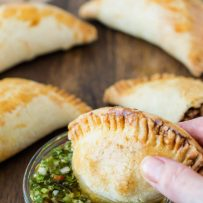A beef and mushroom empanada being dipped into chimichurri sauce
