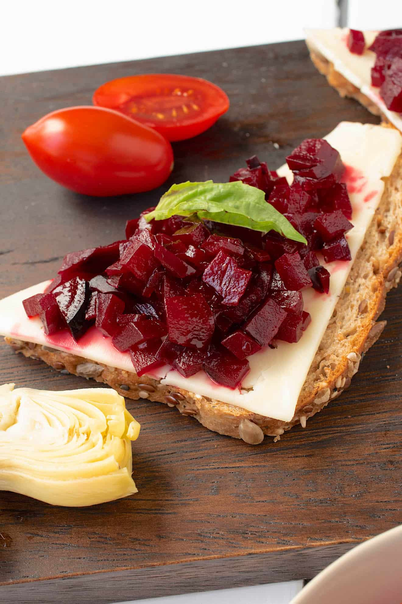 A closeup of the beet relish on top of bread and cheese
