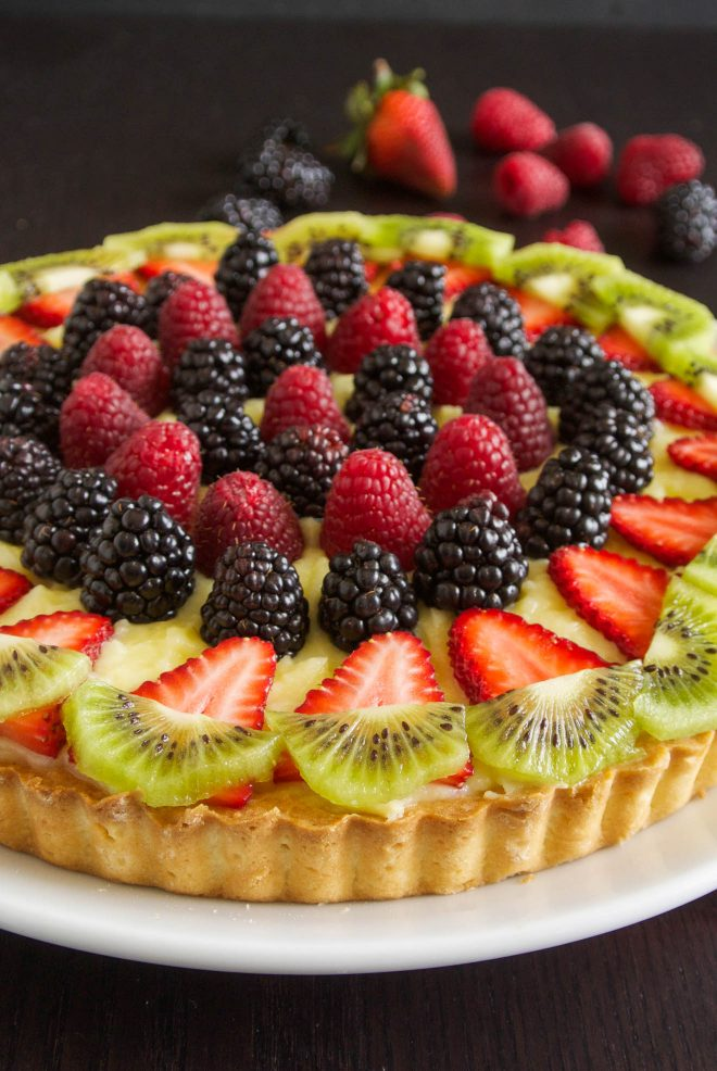 Red, black and green fruit on top of a berry custard tart