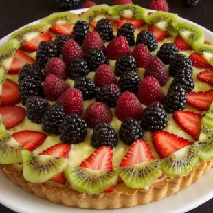 A custard tart decorated with colorful berries and kiwi