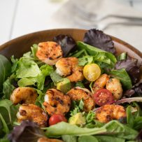 Blackened shrimp nestled on a bed of lettuce with cherry tomatoes and avocado