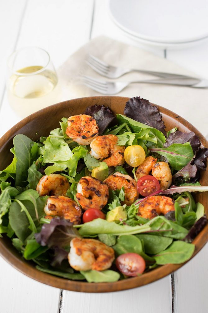 A wood bowl full of lettuce topped with grilled shrimp, red and yellow tomatoes with forks and a glass of wine