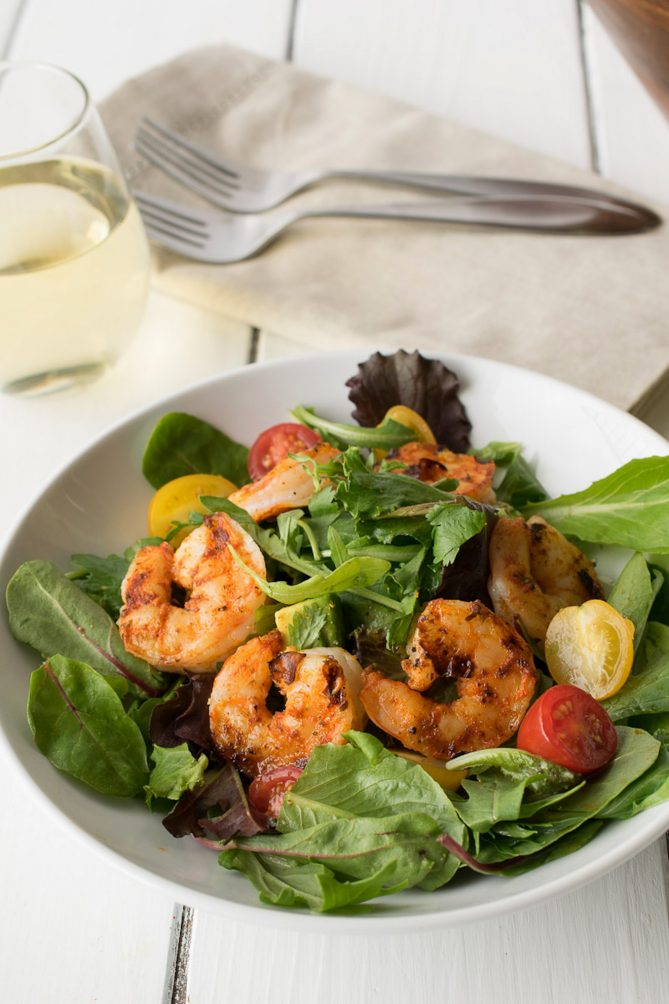 Lettuce, tomatoes, and grilled shrimp on a white plate