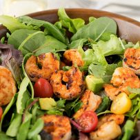 Blackened shrimp in a salad with cherry tomatoes and avocado and lettuce