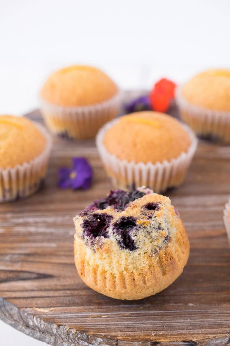 A blueberry orange muffin turned upside down showing the blueberries on the bottom