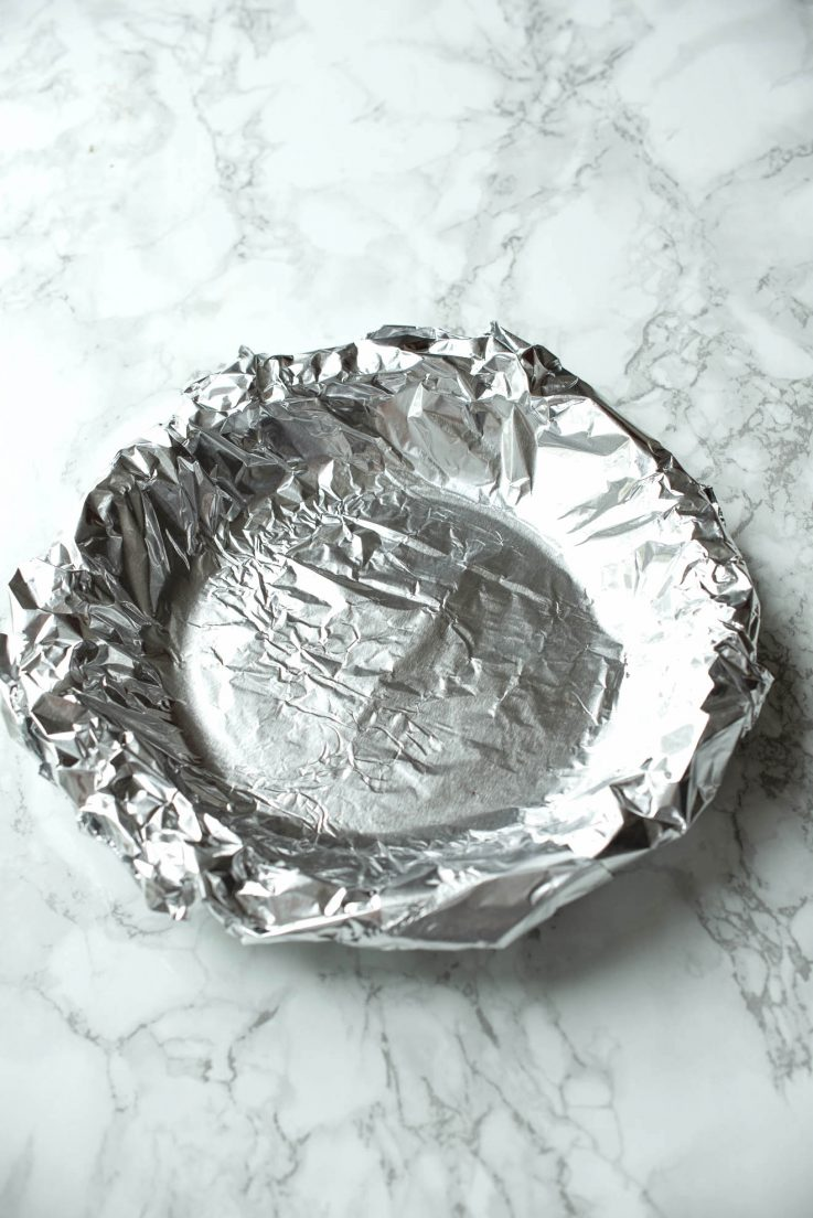A pie crust covered with foil for blind baking