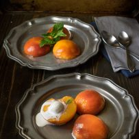3 poached peach halves on pewter plates one topped with ice cream