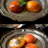 Poached peach halves on a plate with ice cream garnished with fresh mint