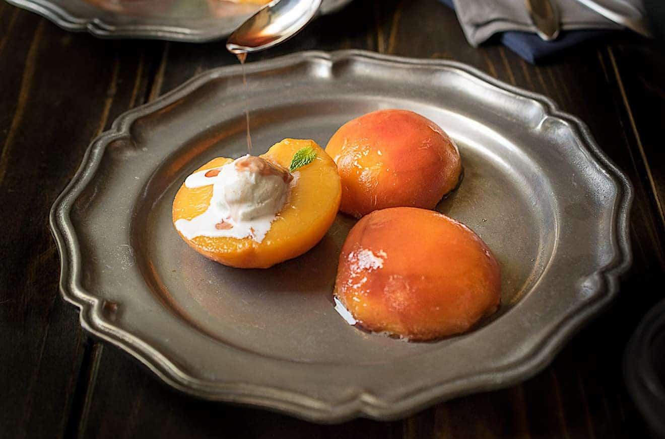 Drizzling bourbon sauce onto peach halves
