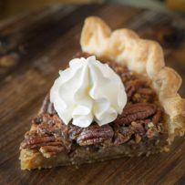 A slice of Bourbon Pecan Pie topped with whipped cream