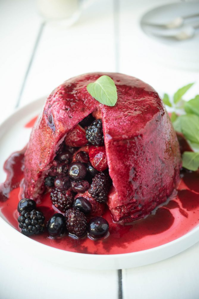 Summer pudding made with bread, cut open with berry fruits pouring out onto a plate