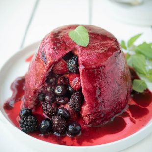 Mixed berries inside a bread pudding covered in colorful berry juice garnished with mint leaves