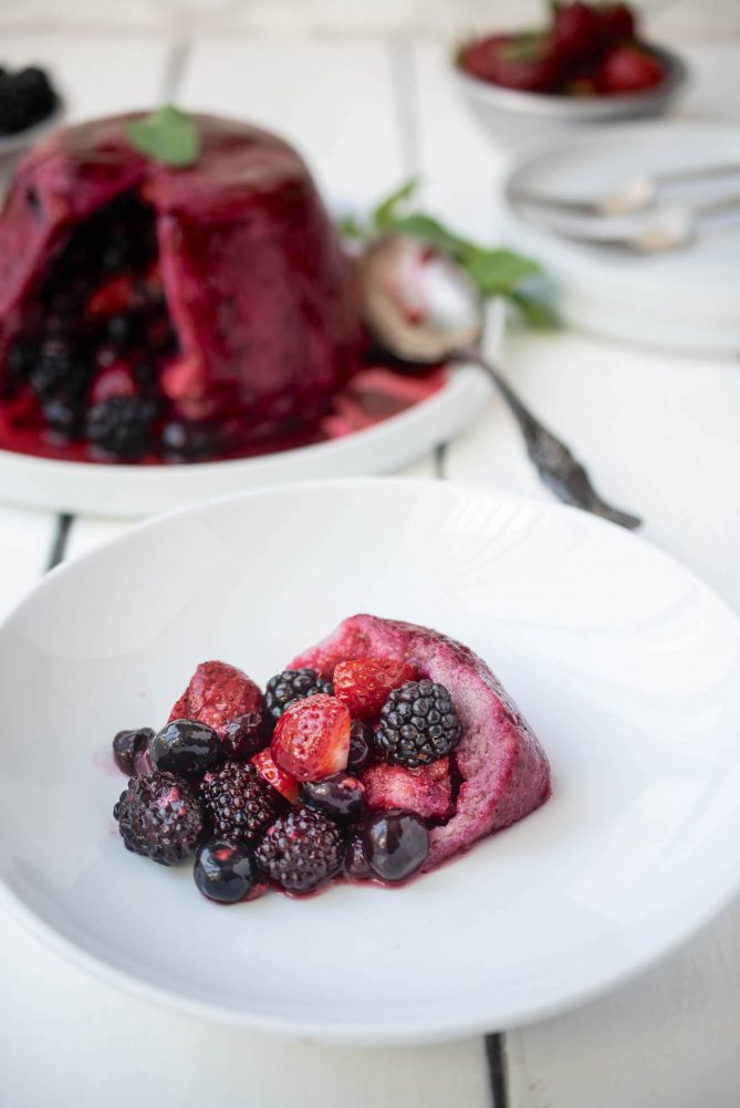 Fresh blackberries, blueberries, strawberries and raspberries in a white bowl with juice soaked bread