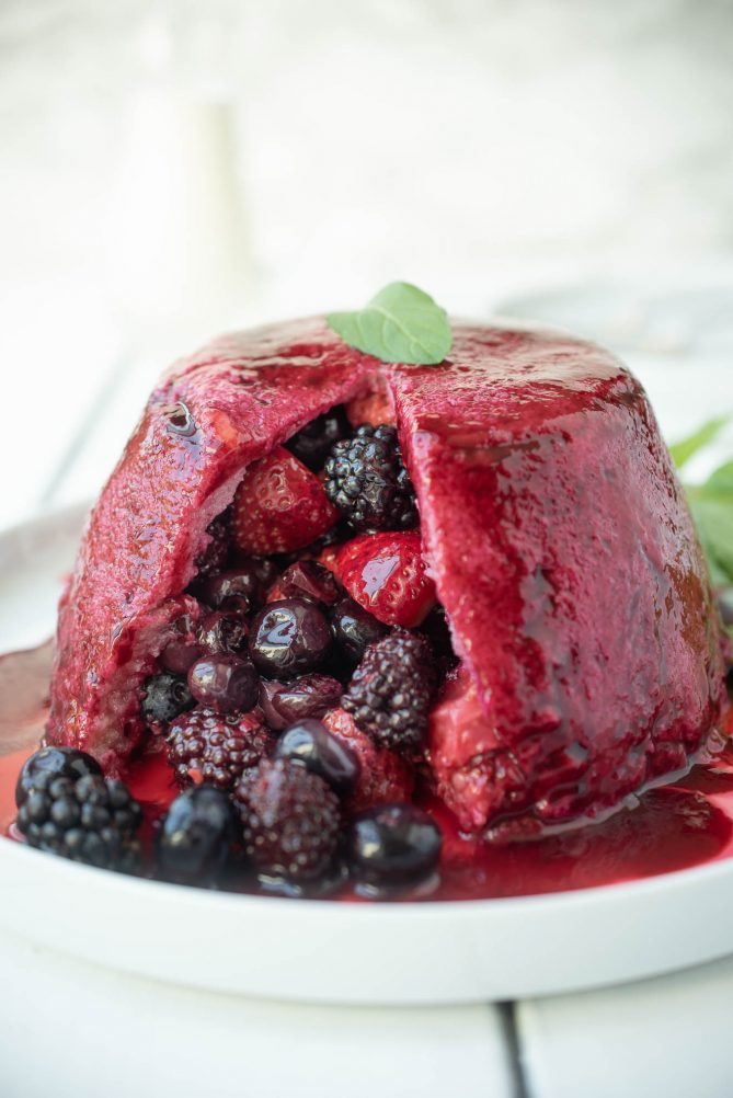 Strawberries, raspberries, blueberries and blackberries spilling out of a bread made pudding