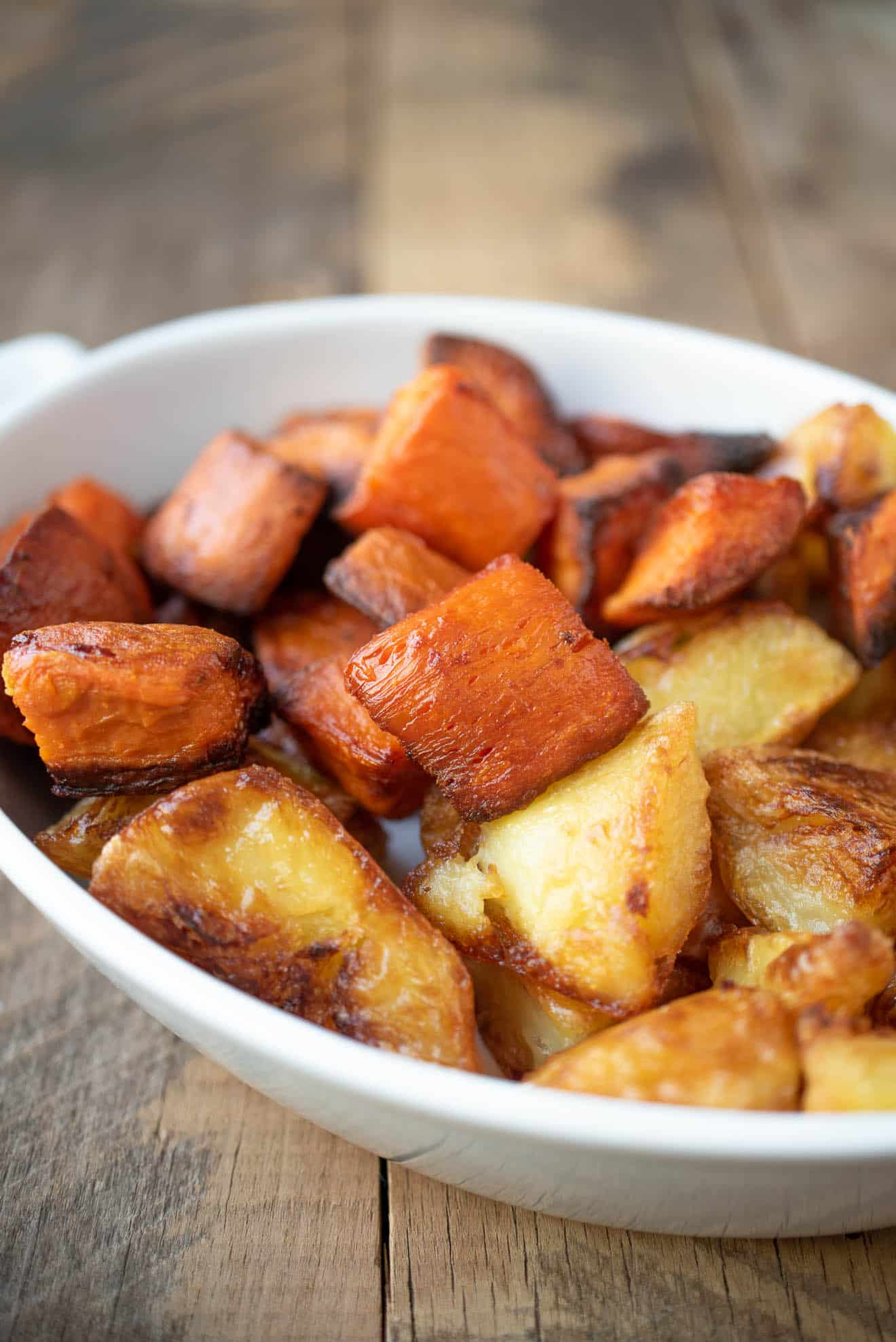 Roasted sweet potatoes/yam and regular potatoes in a white dish