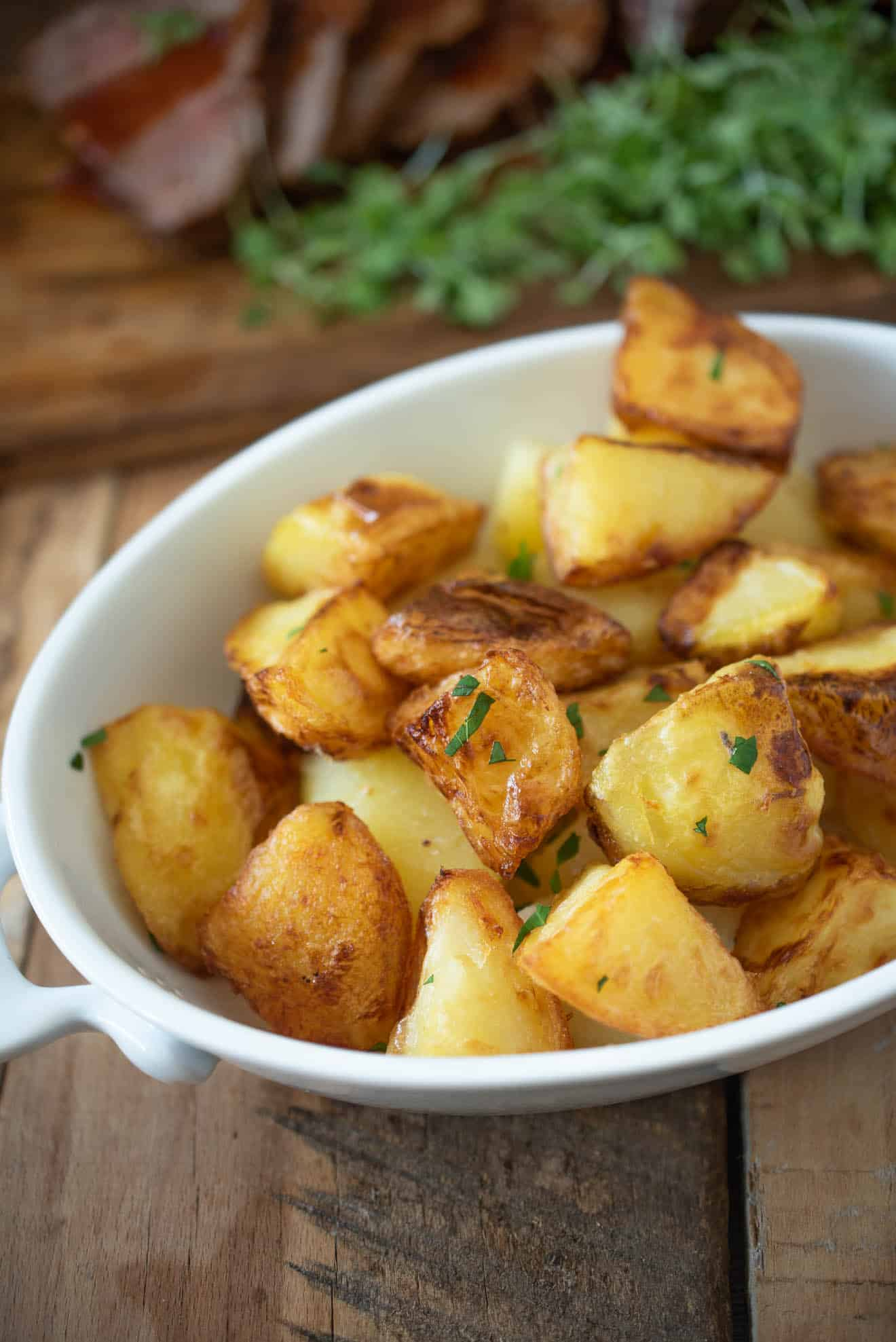 Browned, roasted potatoes in a white oval serving dish