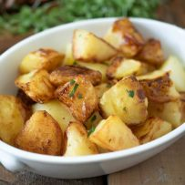 An white oval serving bowl filled with roasted potatoes