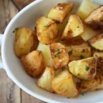 A closeup of British roast potatoes garnished with fresh parsley
