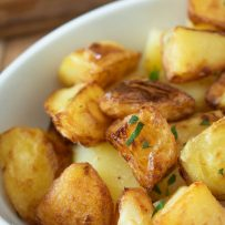 Crispy and browned roast potatoes garnished with chopped parsley