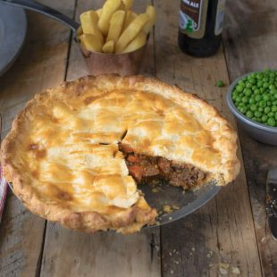 A piece of pie missing showing the chunks of beef and carrots inside