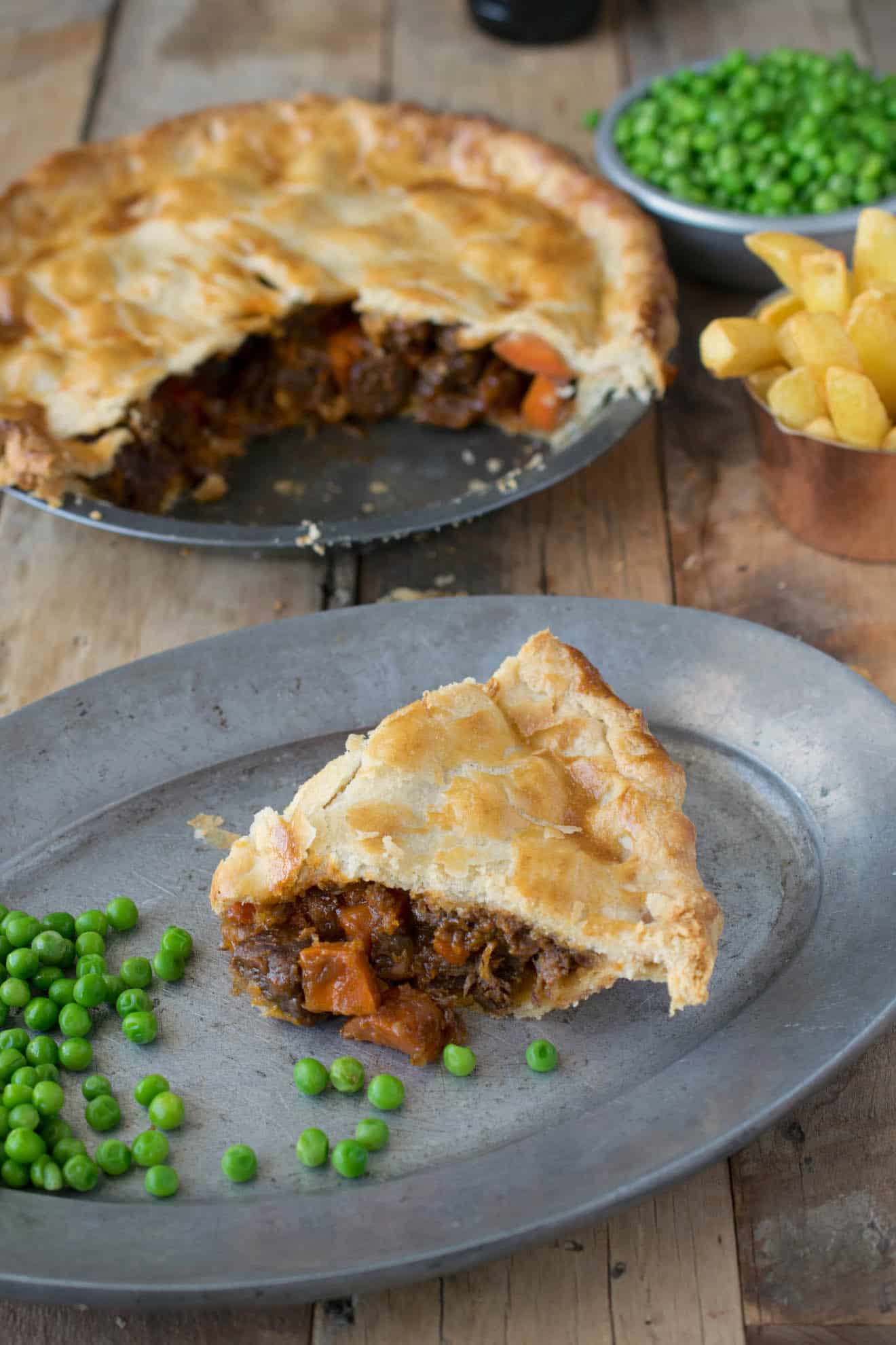 A slice of steak and ale pie on a plate with peas