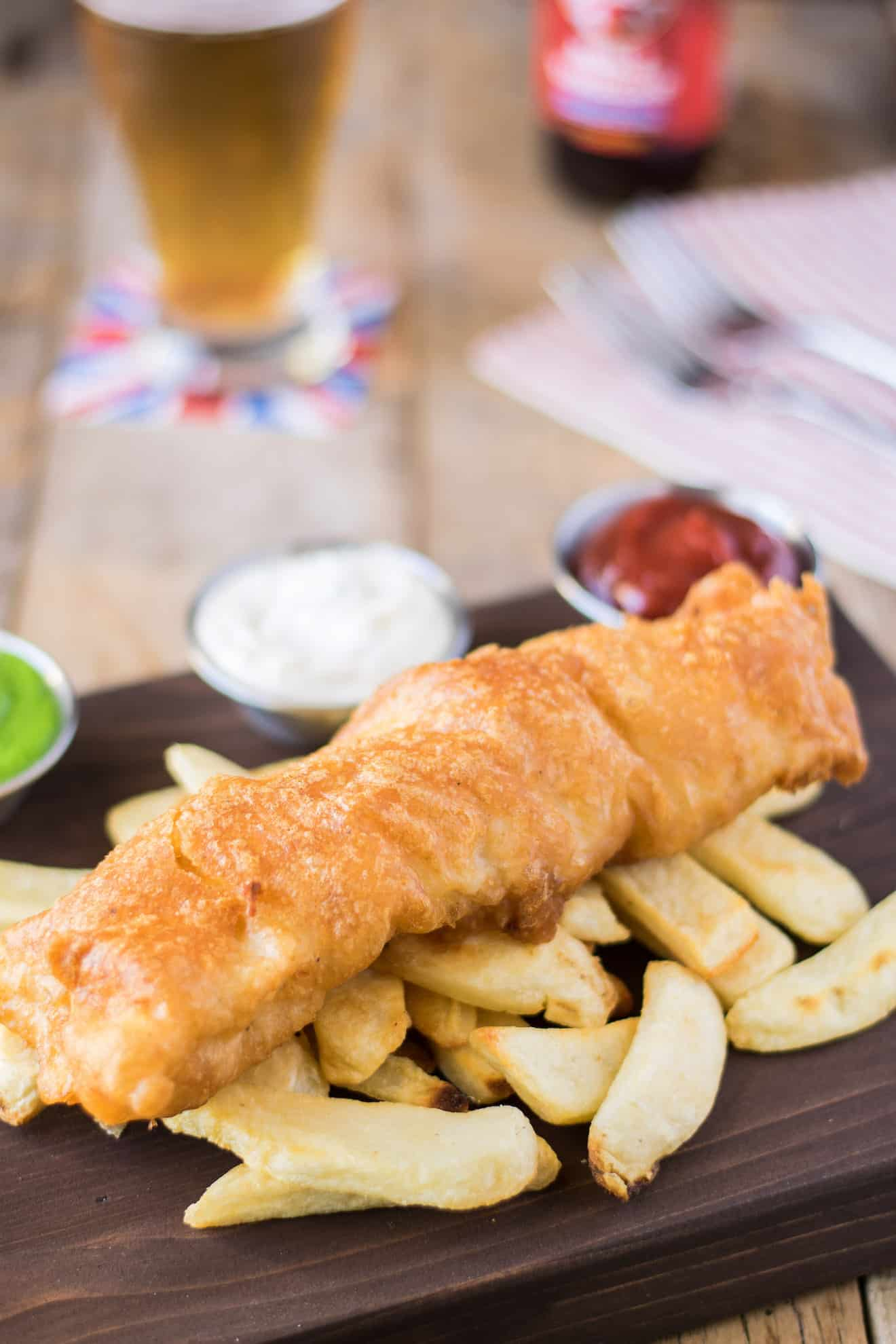 A large piece of fried cod laying on top of chips/French fries