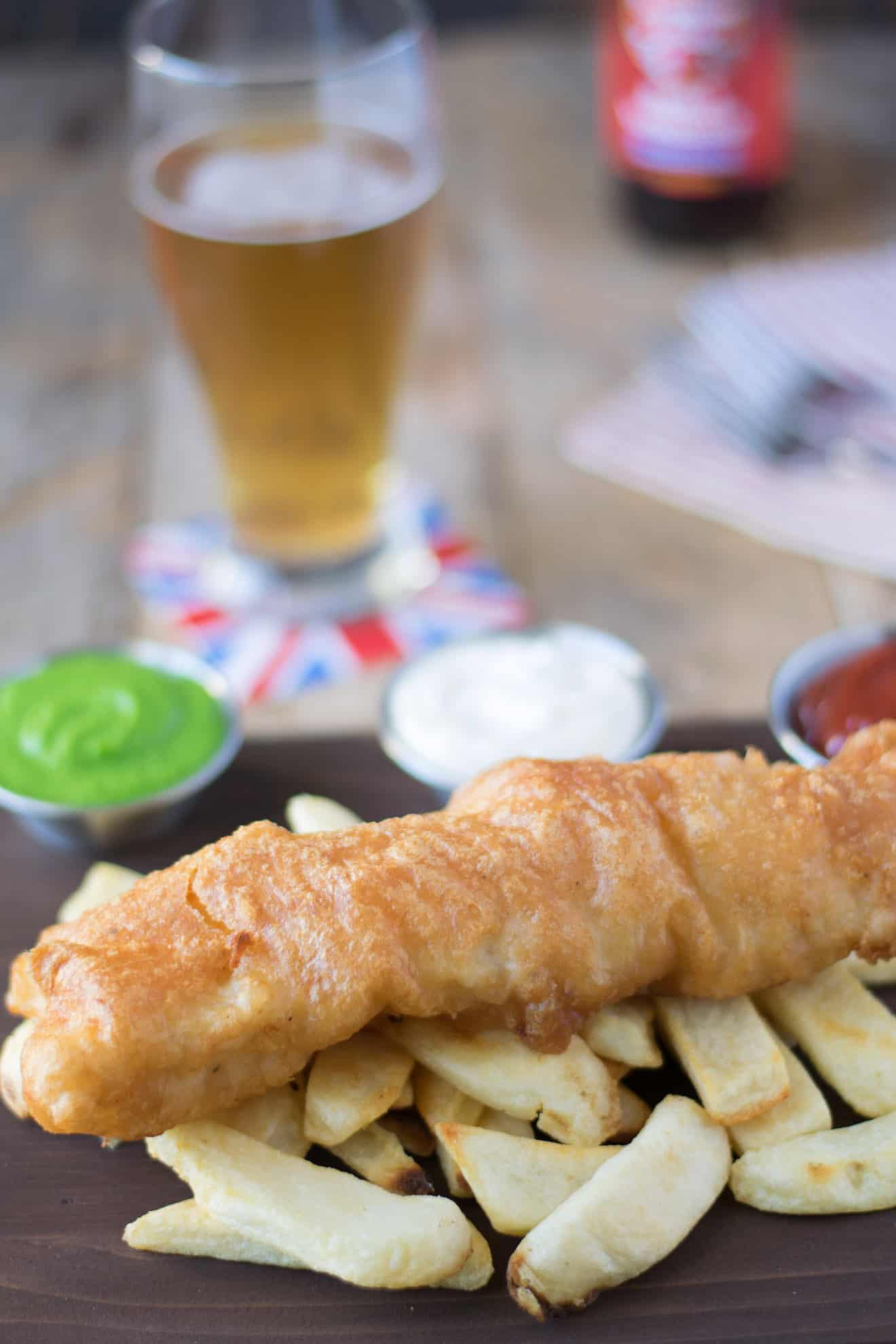 British fish and chips served on a board with a beer and condiments
