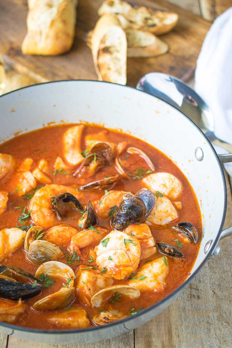 A pan of delicious seafood in tomato broth, brodetto di pesce with toasted bread