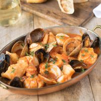 An oval baking dish filled with seafood and shellfish in a tomato broth