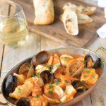 Fish and shellfish in an oval serving dish with a glass of wine and crusty bread