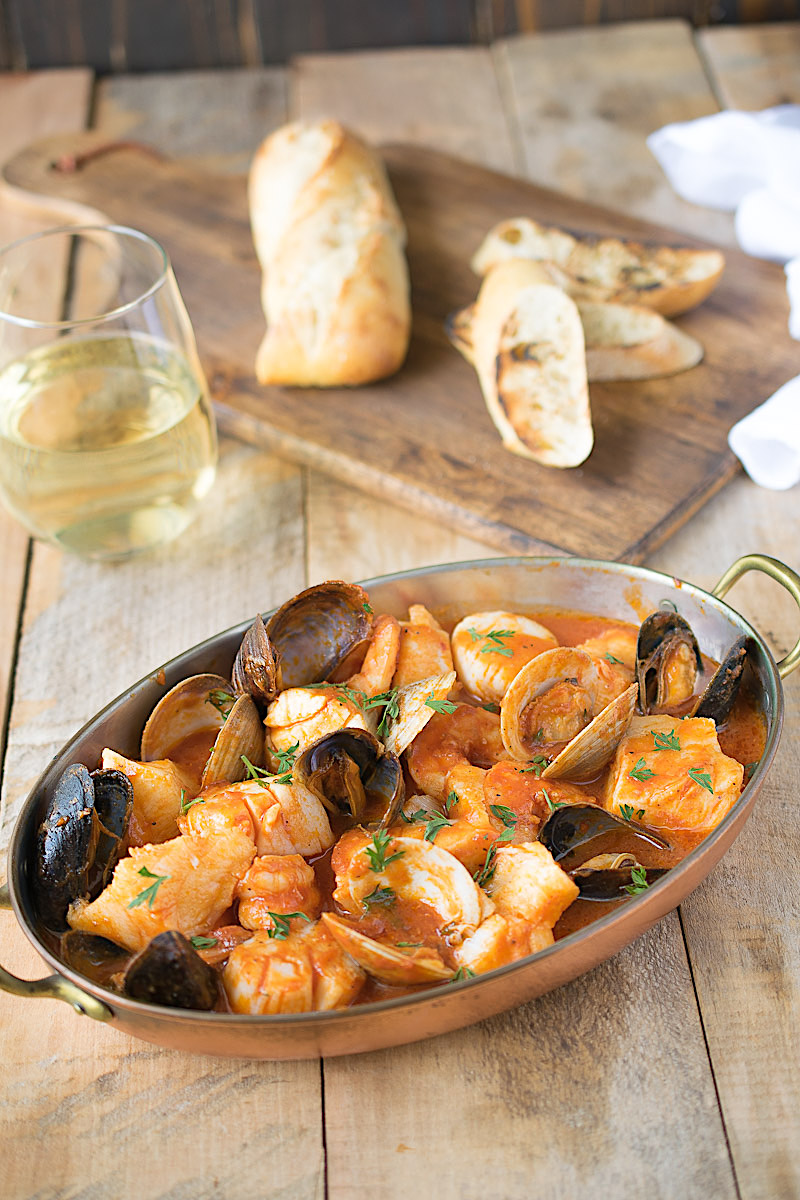 Seafood in broth with a glass of wine and toasted bread